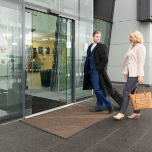 Morland Access Aqua doormat in brown outside a sliding glass entrance door with a man and a woman walking across