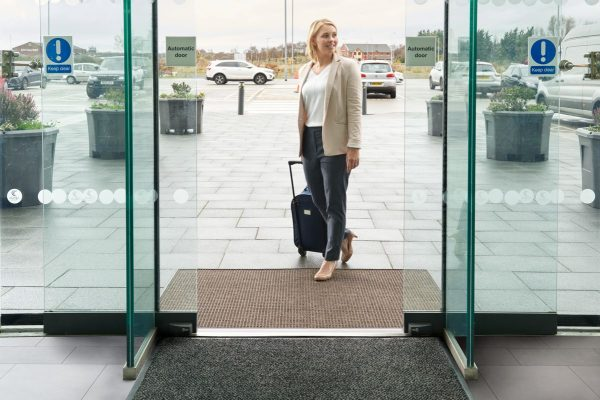 A woman with a flight case on wheels walking over a Morland Access Aqua commercial doormat outdoors by sliding doors