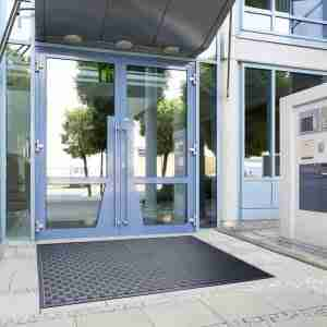 Double door entrance to a building outside which is a Morland Access Approach Industrial doormat