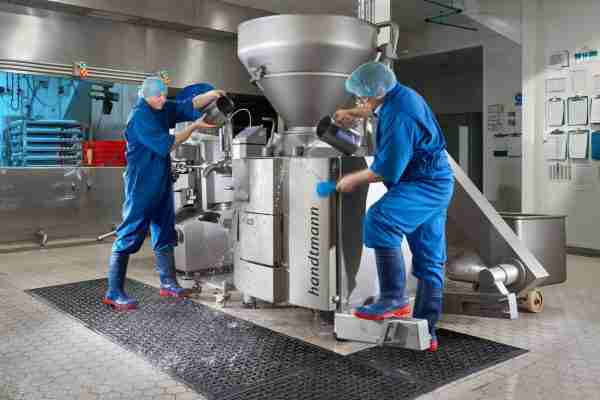 Two people cleaning a food processing area stood on Morland Service Antibacterial rubber industrial doormat