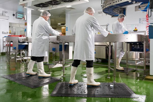 Three people in a food preparation area in white coats and white rubber boots standing on Morland Comfort Industrial Rubber Anti-fatigue mats