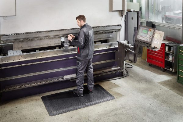 Man at an industrial workstation standing on a Morland Comfort industrial rubber Anti-fatigue mat