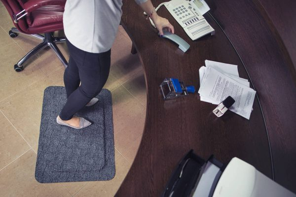 Woman at a desk standing on a Morland Comfort office anti-fatigue mat