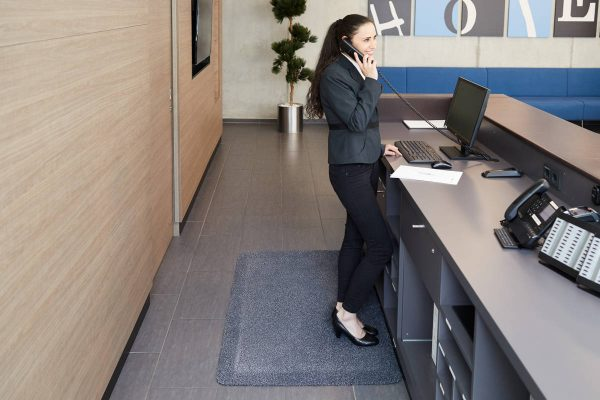 Receptionist standing on a Morland Comfort Soft Top anti-fatigue mat