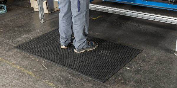 Close up of feet standing a Morland Comfort Structure Anti-fatigue mat at an industrial workstation