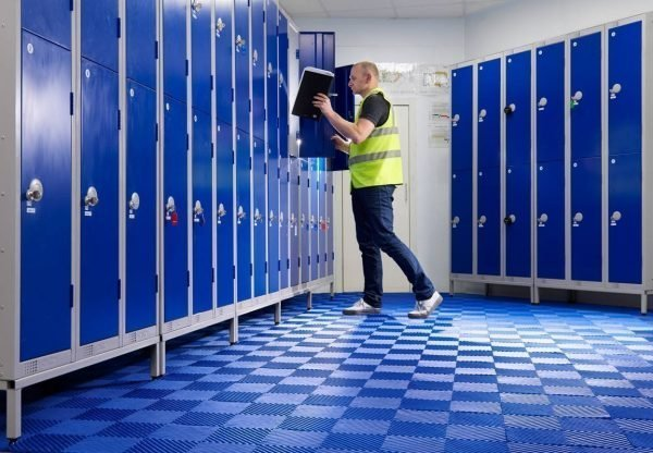a man placing an item in a locker and the floor is covered in the Morland Aqua Step Tile changing room matting in colour dark blue