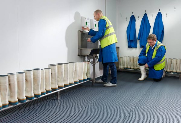 An image of two men in a room with Morland Aqua Step Wave pool matting in Colour Blue installed on the floor one man is washing his hands and the other is putting on a white boot