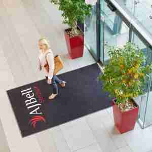 lady walking across a Large doormat in stadium entrance